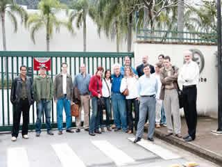 Equipe de jornalistas no portão principal da OPTIGLOBE